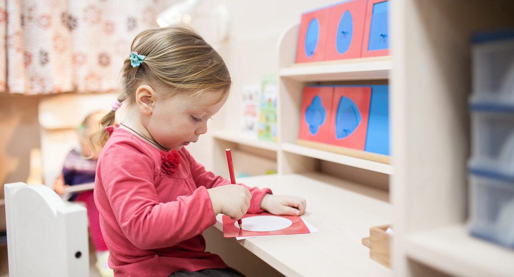 Девочка занимается с металлическими рамками Монтессори в детском саду монтессори в Севастополе
